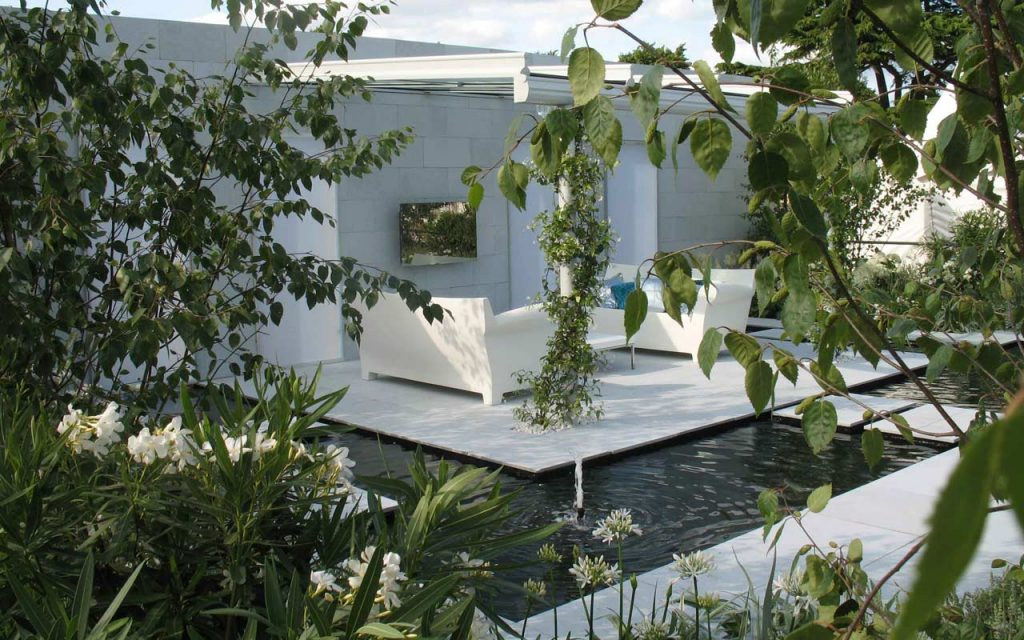 Award winning garden with white sofa and water feature
