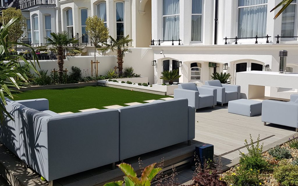 Modern garden with sofas and artificial lawn